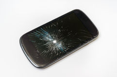 Mobile phone with broken screen. On white table royalty free stock photography