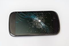 Mobile phone with broken screen. On white table royalty free stock images