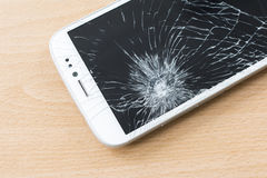 Mobile phone with broken screen. Mobile phone with broken screen on wooden background royalty free stock image