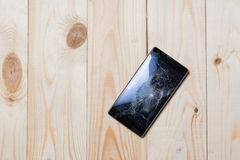 Mobile phone with broken screen. On wooden floor stock photos