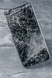 Mobile phone with broken touchscreen on gray background. Mobile phone with broken touchscreen on gray background Repair conzept stock photo