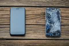 Mobile phone with broken touchscreen on wooden background.  royalty free stock image