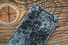 Mobile phone with broken touchscreen on wooden background.  royalty free stock photo