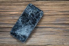 Mobile phone with broken touchscreen on wooden background.  royalty free stock photos