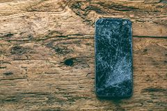 Mobile phone with broken touchscreen on wooden background.  stock photo
