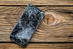 Mobile phone with broken touchscreen on wooden background.  stock images