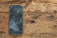 Mobile phone with broken touchscreen on wooden background.  stock photos