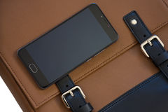 Mobile phone on leather bag. Mobile phone on the brown leather bag royalty free stock image