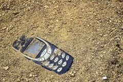 Mobile phone buried in the grey sand. Mobile phone buried in the grey san stock photography