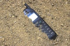 Mobile phone buried in the grey sand. Mobile phone buried in the grey san royalty free stock images