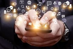Mobile Emits a holographic image of social media related icons. Mobile phone businessman Emits a holographic image of social media related icons Royalty Free Stock Images