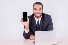 Mobile phone and businessman. Smiling African businessman sittin Royalty Free Stock Photography
