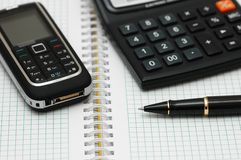 Mobile phone, calculator and p. En on the  notebook Royalty Free Stock Photo