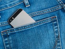 Grey mobile phone with a camera in the back pocket of blue jeans. Mobile phone with camera in the back pocket of blue jeans Stock Photo