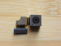 Smartphone camera module. Mobile phone camera module component kept on wooden table stock images