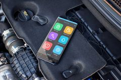 Mobile phone on a car engine with apps for diagnosing car problems.  Stock Photo