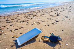 Mobile phone and car keys on beach sand Royalty Free Stock Images