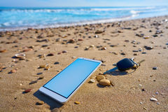 Mobile phone and car keys on beach sand Stock Photo