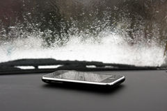 Mobile phone in car with rain Royalty Free Stock Image