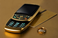 Mobile phone with card and ring Stock Photography