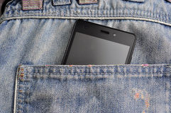 Mobile phone, cellphone in back pocket blue jeans.  Stock Image