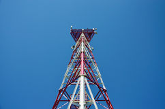 Mobile phone cellular telecommunication radio antenna tower. Cell phone tower against blue sky Stock Image