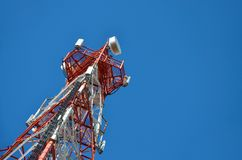 Mobile phone cellular telecommunication radio tv antenna tower against blue sky Royalty Free Stock Photo
