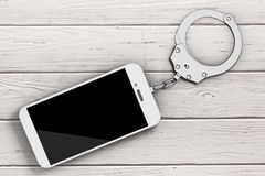Mobile Phone Chained to Metal Handcuffs. 3d Rendering. Mobile Phone Chained to Metal Handcuffs on a wooden table. 3d Rendering Royalty Free Stock Image