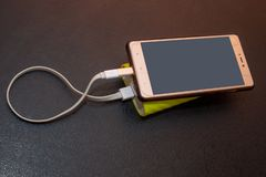 Mobile Phone is charged from power Bank, mobile electricity. Standalone charger stock image
