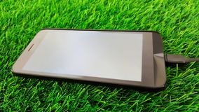 Mobile phone charging  on green grass background. This is mobile phone charging  on green grass background Stock Image