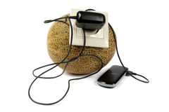 Mobile phone charging from melon Royalty Free Stock Images