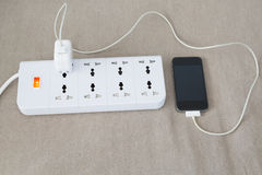 Mobile phone is charging on power cord Royalty Free Stock Images