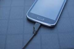 Mobile phone charging with solar energy - charger Stock Image