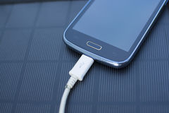 Mobile phone charging with solar energy - charger Royalty Free Stock Photography