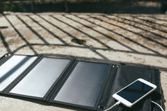 Mobile phone is charging from the solar panel Royalty Free Stock Image