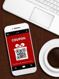 Mobile phone with christmas coupon, laptop and cup of coffee Stock Photography