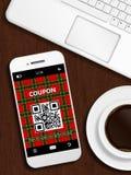 Mobile phone with christmas coupon, mug of coffee and laptop key Stock Photography