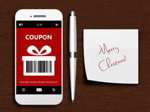 Mobile phone with christmas coupon, pen and christmas wishes. Lying on wooden desk royalty free stock photos