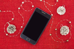 Mobile phone and the Christmas decoration Royalty Free Stock Photo