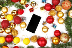 Mobile phone with Christmas gifts and finery. New year shopping with decoration Royalty Free Stock Image