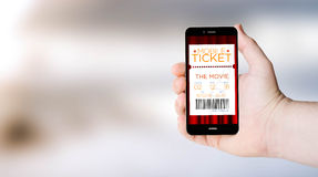 Mobile phone cinema tickets shopping on user´s hand Royalty Free Stock Image