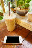 mobile phone with class of iced cappuccino on the table, coffee Royalty Free Stock Image