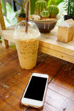 mobile phone with class of iced cappuccino on the table, coffee Royalty Free Stock Photo
