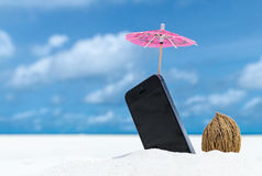Mobile phone and cocktail umbrella on the beach Royalty Free Stock Image