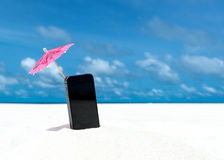 Mobile phone and cocktail umbrella on the beach with the sea Royalty Free Stock Images