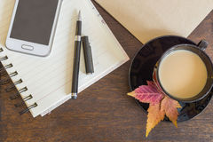 Mobile phone, coffee with autumn leaves, notebook and craft paper on wooden deck Stock Photography