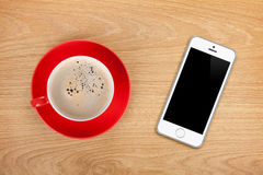 Mobile phone and coffee cup Stock Images