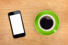 Mobile phone and coffee cup Stock Photos
