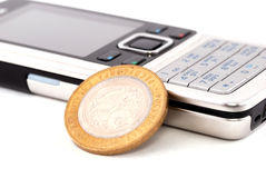 Mobile phone and coin. Mobile phone and golden coin Stock Images