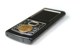 Mobile phone and coin Royalty Free Stock Photos